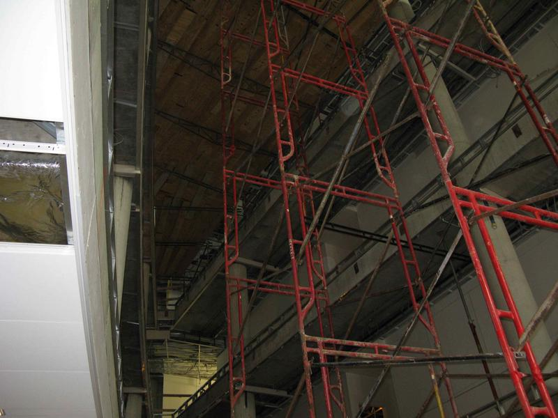 View from below of scaffolding and platform across atrium. The platform is being used to help with the installation of the ceiling trim, lights and other finishing work at the fourth floor level and above.