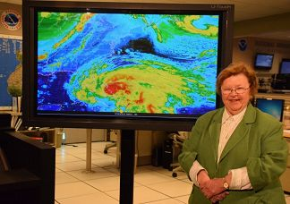 U.S. Senator Barbara Mikulski standing in front of a display showing a hurricane event.
