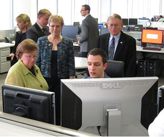Figure 1: (left to right, foreground) U.S. Senator (MD) Barbara Mikulski, NOAA Administrator Jane Lubchenco, and HPC Director Jim Hoke discuss the forecast track of Sandy with HPC forecaster Sean Ryan (seated). Photo courtesy Ed Danaher (HPC).