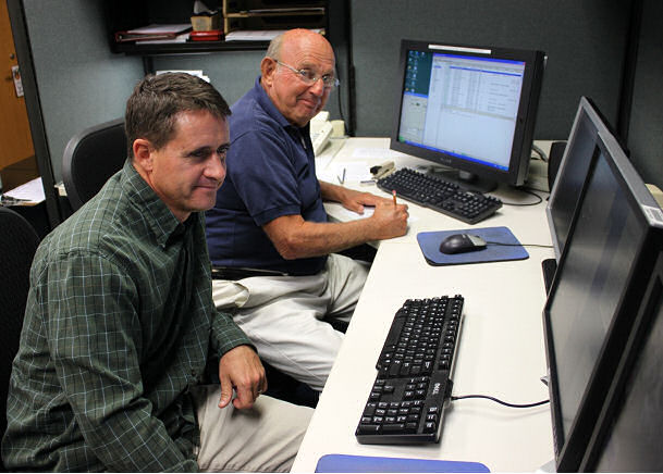 Dave Nolan, Ph.D. (left), of the University of Miami, shadows John Pavone of NHC's CARCAH unit, discussing data being received from Hurricane Hunter aircraft.