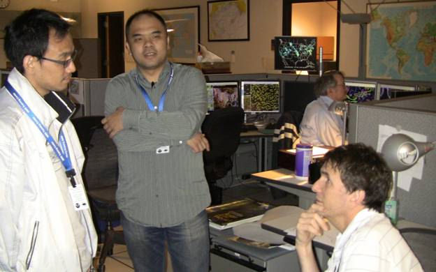 Taiwanese meteorologists Tim Chang(left) and Bois Chang discuss the forecast with AWC meteorologist Scott Tansey (seated).