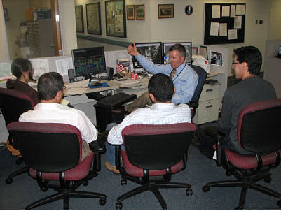 HPC International Desk Coordinator Michel Davison leads a discussion with visiting forecasters.
