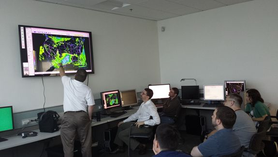 Participants in the 2014 Flash Flood and Intense Rainfall Experiment discuss the morning's forecast (photo credit: Tom Workoff). Clockwise from the front: Greg Waller (WGRFC, standing), Patrick Burke (WPC), Randy Graham (WFO SLC), Kelly Mahoney (ESRL), Eric Aligo (EMC), Jason Elliot (WFO LWX), and Ryan Husted (WFO GLD).